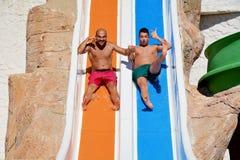 Dos hombres que montan abajo de los diapositiva-amigos de un agua que gozan de un tubo del agua montan Fotos de archivo