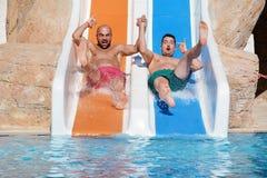 Dos hombres que montan abajo de los diapositiva-amigos de un agua que gozan de un tubo del agua montan Imagen de archivo libre de regalías
