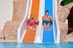 Dos hombres que montan abajo de los diapositiva-amigos de un agua que gozan de un tubo del agua montan Imagenes de archivo