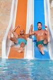 Dos hombres que montan abajo de los diapositiva-amigos de un agua que gozan de un tubo del agua montan Fotografía de archivo