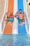 Dos hombres que montan abajo de los diapositiva-amigos de un agua que gozan de un tubo del agua montan Fotos de archivo libres de regalías