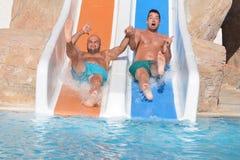 Dos hombres que montan abajo de los diapositiva-amigos de un agua que gozan de un tubo del agua montan Foto de archivo