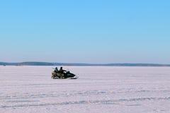 Dos hombres que montan en un invierno de la moto de nieve Imágenes de archivo libres de regalías
