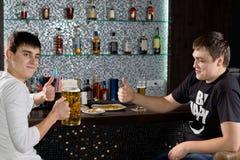 Dos hombres que muestran los pulgares para arriba mientras que bebe la cerveza Imágenes de archivo libres de regalías