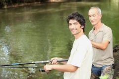 Dos hombres que pescan con caña al lado del río Fotos de archivo
