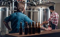 Dos hombres que presentan la cerveza del arte en el microbrewery Imagen de archivo