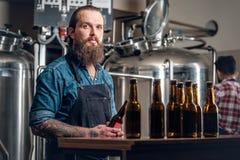 Dos hombres que presentan la cerveza del arte en el microbrewery Foto de archivo libre de regalías