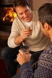 Dos hombres que relajan sentarse en el whisky de consumición del sofá imagen de archivo libre de regalías