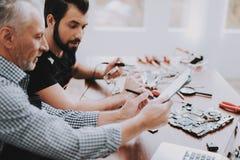 Dos hombres que reparan el equipo del hardware en taller fotos de archivo
