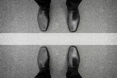Dos hombres que se colocan en la línea blanca Foto de archivo libre de regalías
