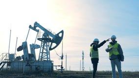 Dos hombres que se colocan en un campo en un fondo de la torre del aceite almacen de video
