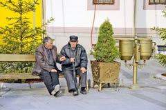 Dos hombres que se sientan en banco en Bitola imagenes de archivo