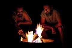 Dos hombres que se sientan en una hoguera en la noche, barbacoa y acampando en Imagen de archivo