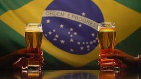 Dos hombres que sostienen los vasos de cerveza, bandera brasileña en el fondo, Día de la Independencia metrajes
