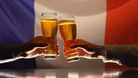 Dos hombres que tintinean los vasos de cerveza, bandera francesa en el fondo, celebración del día de fiesta almacen de metraje de vídeo