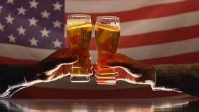 Dos hombres que tintinean los vidrios de cerveza contra la bandera de los E.E.U.U., celebración del Día de la Independencia almacen de metraje de vídeo