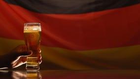 Dos hombres que toman los vidrios de cerveza, bandera alemana en el fondo, celebración del día de fiesta almacen de metraje de vídeo
