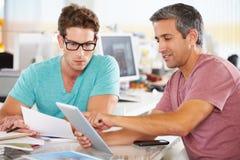 Dos hombres que usan el ordenador de la tablilla en oficina creativa