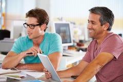 Dos hombres que usan el ordenador de la tablilla en oficina creativa Foto de archivo libre de regalías