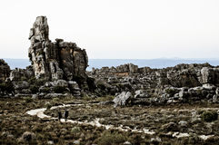 Dos hombres que van de excursión entre las rocas Imágenes de archivo libres de regalías