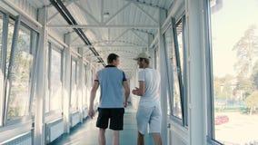Dos hombres que van a través del pasillo y de hablar almacen de metraje de vídeo