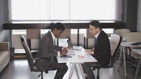 Dos hombres se sientan en butacas en la oficina y hablar almacen de metraje de vídeo