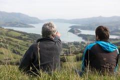Dos hombres se sientan en el top de la colina y miran el puerto Imagen de archivo