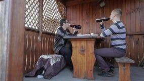 Dos hombres se sientan en la tabla y beben la cerveza de las botellas plásticas Feliz almacen de metraje de vídeo