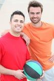 Dos hombres sonrientes con la bola de la cesta Foto de archivo libre de regalías