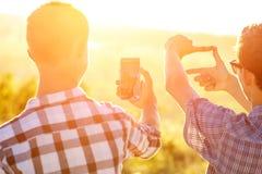Dos hombres toman las imágenes de la puesta del sol en el teléfono en el sol imagenes de archivo
