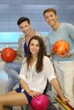Dos hombres y la muchacha con las bolas en el bowling aporrean Fotografía de archivo libre de regalías