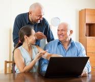 Dos hombres y mujer en el ordenador portátil Imagen de archivo libre de regalías