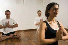 Dos hombres y mujer que realizan la yoga - horizontal Fotos de archivo libres de regalías