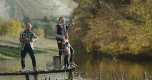 Dos hombres y un pescado de cogida del niño pequeño del lago con la caña de pescar dos almacen de metraje de vídeo
