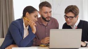 Dos hombres y una mirada de la mujer en el ordenador portátil almacen de video