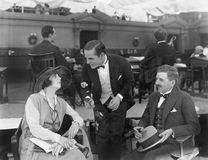 Dos hombres y una mujer en un restaurante en el embarcadero (todas las personas representadas no son vivas más largo y ningún est Fotos de archivo