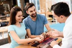 Dos hombres y una mujer están discutiendo la compra de los nuevos muebles Imagen de archivo