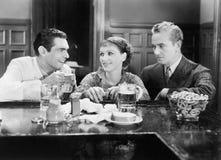 Dos hombres y una mujer que se sienta en las cervezas de consumición de una barra (todas las personas representadas no son vivas  Imagenes de archivo