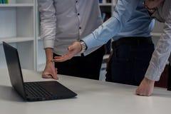 Dos hombres y una mujer que trabaja en un proyecto corporativo Hombre en el b Imagen de archivo libre de regalías