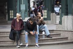 Dos hombres y una mujer se están sentando en los pasos cerca de los amigos que esperan del metro para Imágenes de archivo libres de regalías