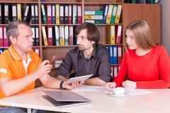 Dos hombres y una mujer tienen reunión en oficina Imagen de archivo libre de regalías