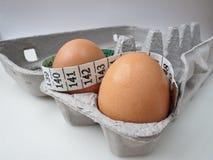 Dos huevos en cartón con la cinta de medición 2 Imágenes de archivo libres de regalías