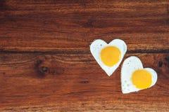 Dos huevos fritos en forma de corazón en fondo de madera fotografía de archivo