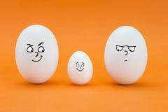 Dos huevos grandes miran con la cara de pocos amigos un pequeño huevo Fotos de archivo