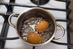 Dos huevos marrones están hirviendo en un pequeño pote en una cocina blanca en la cocina foto de archivo libre de regalías