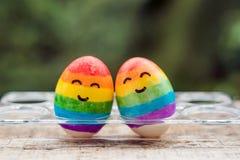 Dos huevos se colorean en los colores del arco iris como bandera de g fotografía de archivo