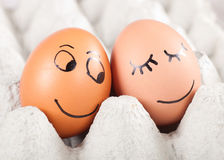 Dos huevos sonrientes divertidos en un paquete Imagen de archivo libre de regalías