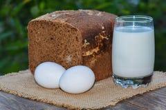 Dos huevos y pan de centeno cocido del corte, vidrio con leche Foto de archivo