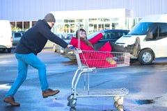 Dos inconformistas felices que se divierten en el carro de la compra al aire libre Fotografía de archivo libre de regalías