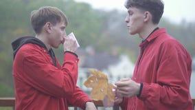 Dos individuos alegres jovenes gastan a amigos del tiempo al aire libre juntos para pasar la amistad masculina del tiempo al aire metrajes